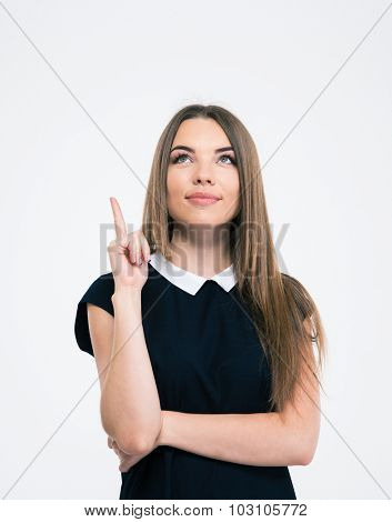 Portrait of a pretty thoughtful woman pointing finger up at copyspace isolated on a white background