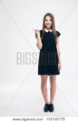 Full length portrait of a smiling woman pointing finger away isolated on a white background