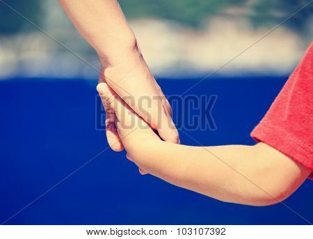 mother and son holding hands at sea
