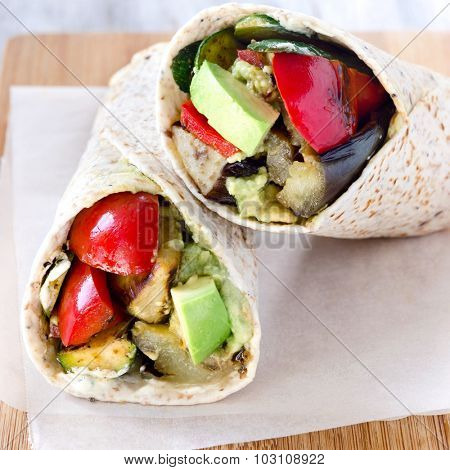 Healthy vegetarian vegan burrito wraps with roasted vegetables like aubergine eggplant, red bell peppers, avocado