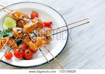 Grilled chicken skewers served with tomatoes lime and coriander on a rustic enamel plate