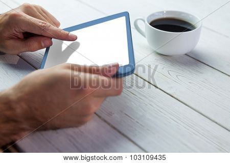 Cropped image of person holding tablet on wooden desk