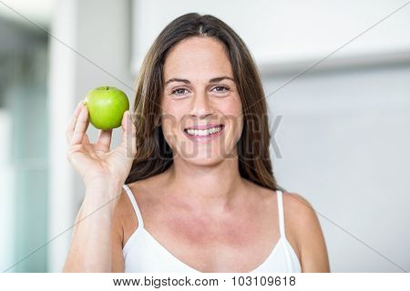 Portrait of pregnant woman holding Granny Smith in room