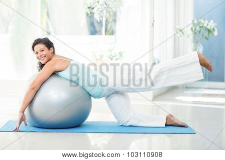 Full length portrait of smiling pregnant woman stretching with exercise ball on mat at fitness studio