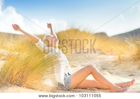 Woman relaxing on sand dunes.