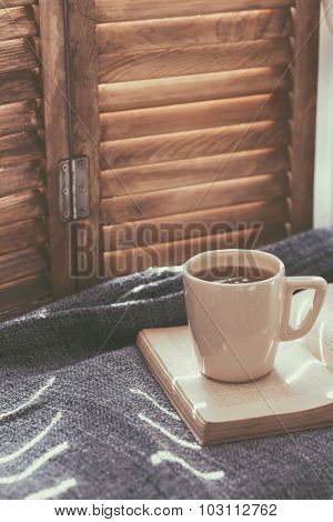Warm and cozy window seat with cushions and a opened book, light through vintage shutters, rustic style home decor. (Text in the book is not readable, because if was transformed by filter).