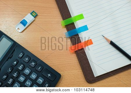 Pencil,note Paper,calculator ,usb And Book On Wooden Table. Top View