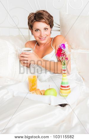 Nice woman sitting in bed with cup of coffee