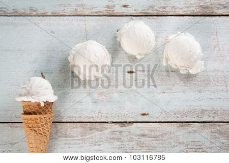 Top view scoop vanilla ice cream in waffle cone on wood background.