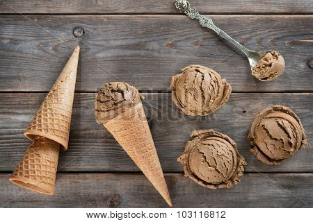 Top view cocoa ice cream in waffle cone on old rustic vintage wooden background.
