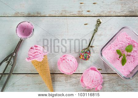 Top view pink ice cream in waffle cone with utensil on rustic wooden background.
