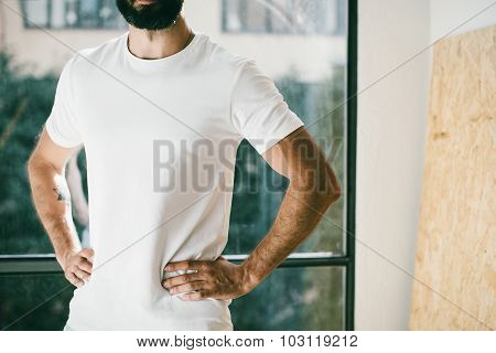 Portrait of a bearded man wearing white tshirt with window