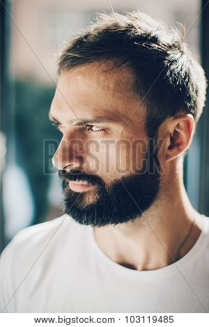 Portrait of a bearded man looking out the window