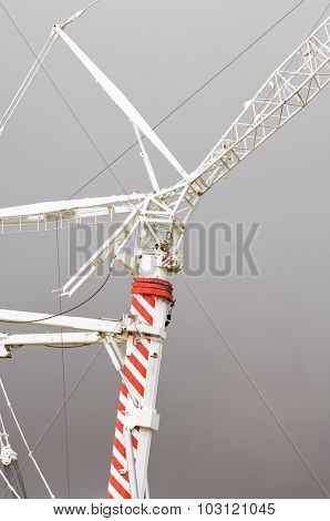 detail of a red and white crane with stormy sky
