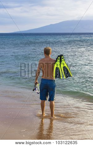 Rear view of an attractive man going snorkeling in Hawaii