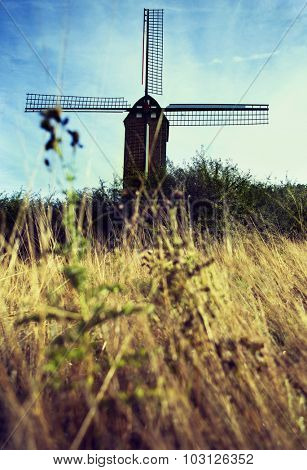 old Belgian windmill standing on the summer meadow with yellow grass against blue sky, focus on the mill