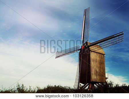 old Belgian windmill standing on the summer meadow against blue sky