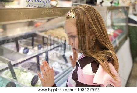 Little girl looking at cakes display in shop
