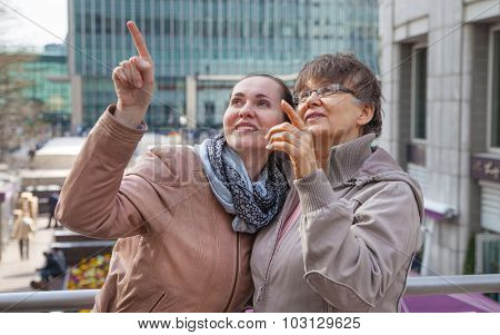 Outdoor family portrait of pension age Mother and her daughter in the city, smiling and looking arou