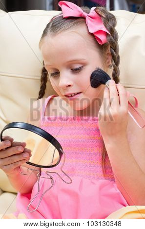 Little girl puts makeup on sofa