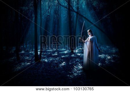 Young elven girl with sword at night forest