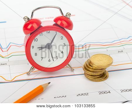 Alarm clock with coins and pencil