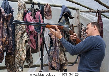 Hunter Cleaning Gun In The Camp