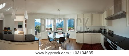 Interior of a furnished house, kitchen and dining room with glass table