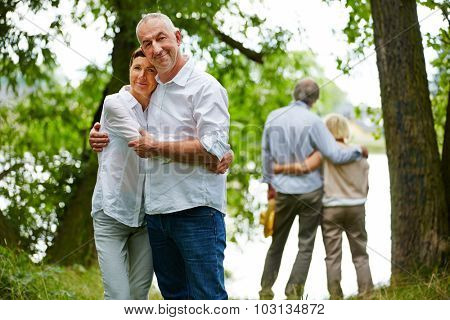 Two happy senior couples embracing in garden of retirement home