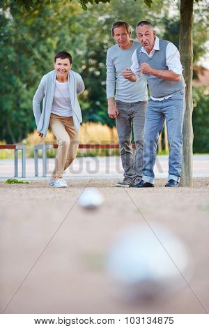 Woman playing boule with group of seniors in summer and throwing her ball