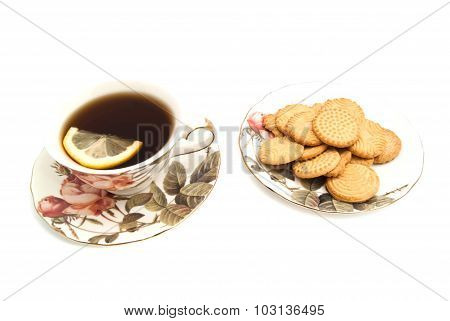 Mug Of Tea With Lemon And Some Cookies On White