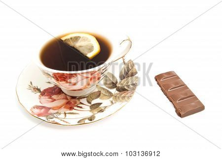 Mug Of Tea With Lemon And Chocolate Bar On White