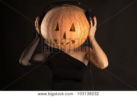 woman with a pumpkin on head with headphones listening music