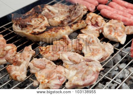 Stilts raw chicken and sausages on the barbecue