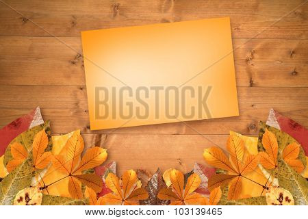 Orange card against autumn leaves on wood