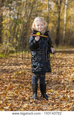 little girl wearing rubber boots in autumnal nature