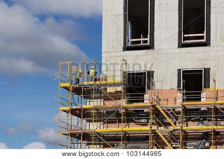 Construction Workers On Scaffolding - Building Facade Construction Site
