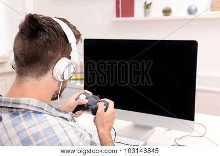 Young man playing computer games at home