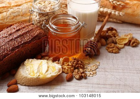 Healthy breakfast with bread, honey, nuts on table, on colorful background. Country breakfast concept