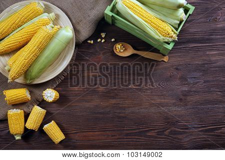 Ripe corn on sacking on wooden background