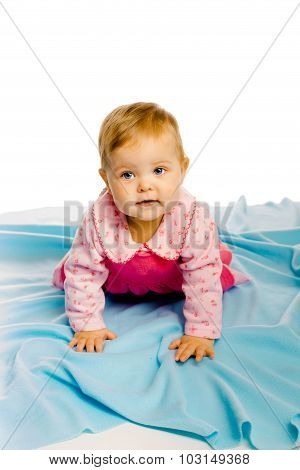 Baby Girl Crawling On The Blue Coverlet. Studio
