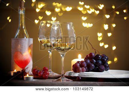 Wine glass near bottle on hearts bokeh background