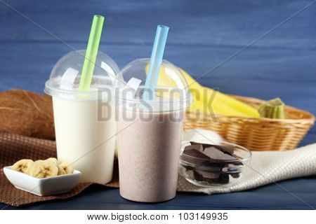 Plastic cup of milkshake with banana on color wooden background