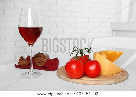 Glass of wine with cheese and tomatoes on table in kitchen