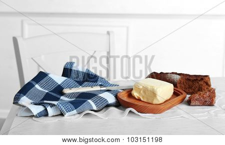 Fresh bread and butter on table in kitchen