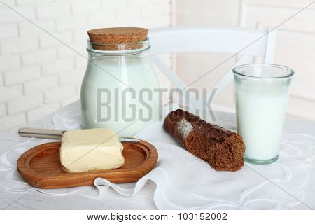 Milk with bread and butter on table in kitchen