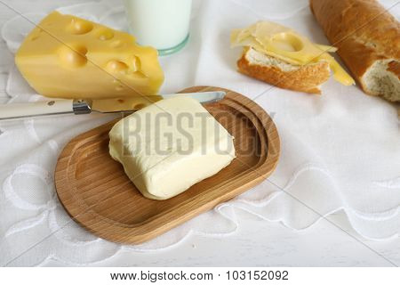 Fresh bread with cheese and butter on table close up