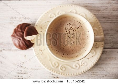 Cup of coffee with chocolate zephyr on wooden table, top view