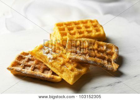 Sweet homemade waffles on tray, on light background