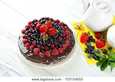 Delicious chocolate cake with summer berries on white wooden background